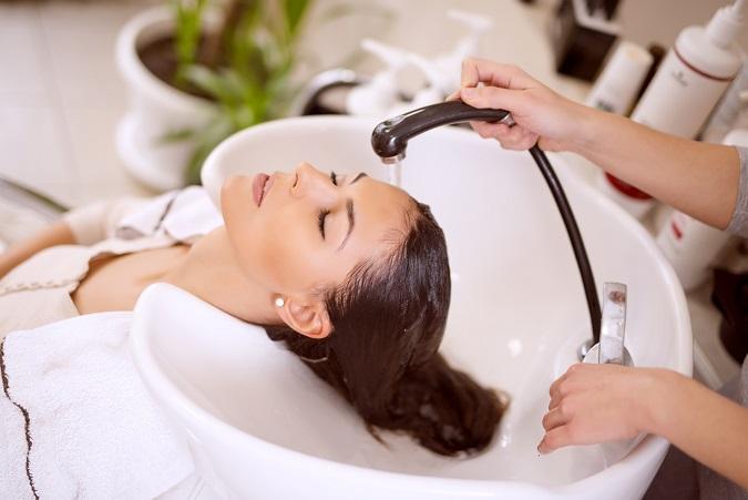 Young woman washing hair in salon