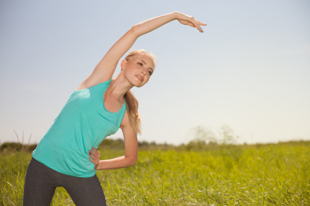 Sport beauty  blond young  woman exercising in the outdoors yoga