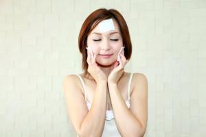 スキンケアをしてリラックスしている笑顔の女性
