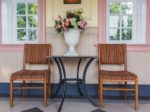 Two chairs and table with bouquet of flowers in vase on a patio