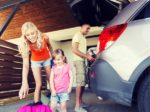 happy family packing things to car at home parking