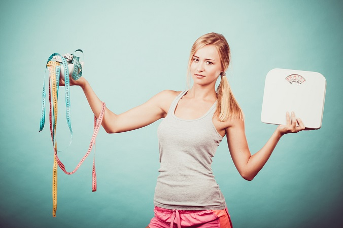 Girl with scales measuring tapes. Weight loss.