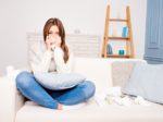 Sick  girl with fever sneezing in tissue sitting on sofa, close