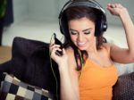 Smiling woman with headphones listen to music