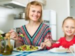 Woman and little girl eating at kitchen.