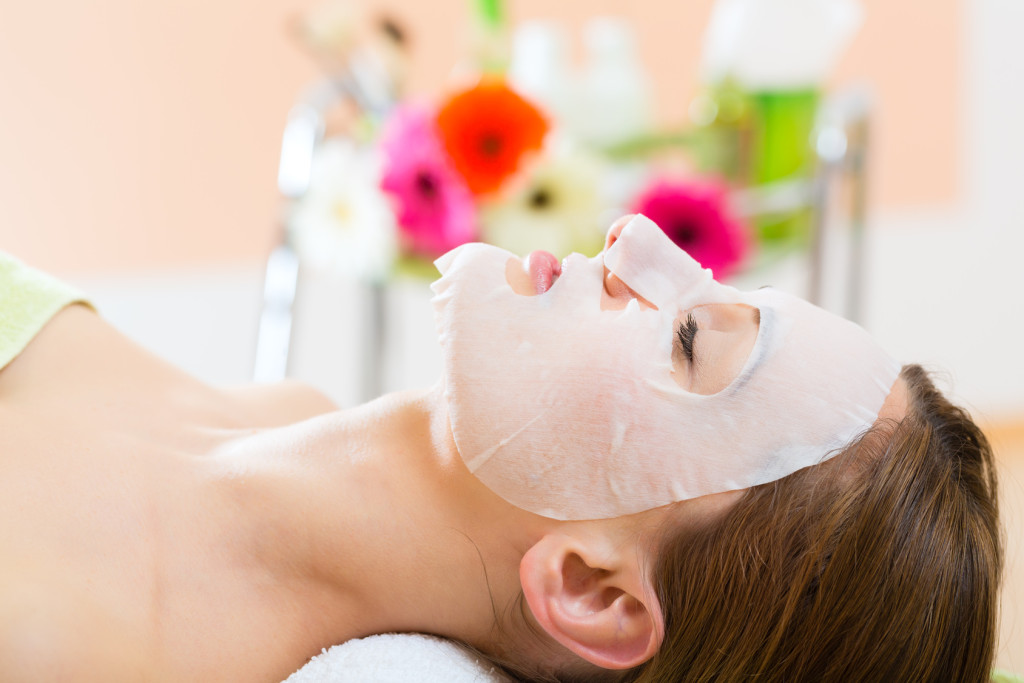 Wellness - woman receiving facial mask in spa for clean skin