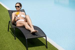 プールサイドで日焼けする女性