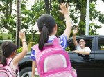 little girls say good bye with father in front of school