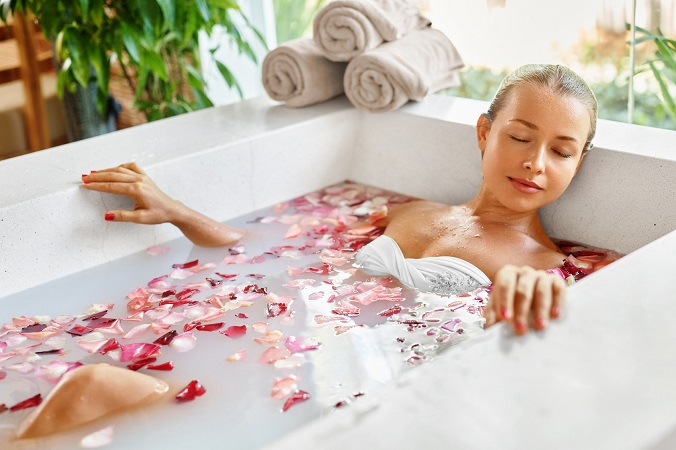 Woman In Spa Flower Bath. Aromatherapy. Closeup Portrait Of Beautiful Sexy Young Female Relaxing In Rose Bath Tub In Resort Day Spa Salon. Beauty Treatment. Skin Body Care. Healthy Lifestyle Concept