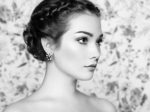 Portrait of young beautiful woman on a background of flowers. Fashion photo. Jewelry and hairstyle. Perfect makeup. Black and White
