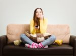 Young woman spends his free time watching TV on the couch at hom