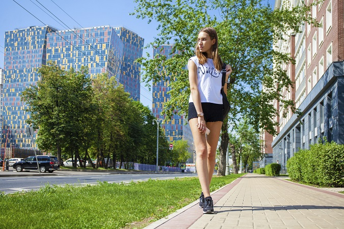 Young beautiful woman in black short walking on the summer stree