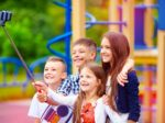 group of happy friends taking selfy on smart phone, outdoor playground
