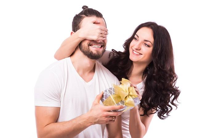 Attractive happy woman with big toothy smile holding boyfriends eyes giving him a present for Valentine's day. Caucasian couple. White background.