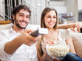 家で映画を見るカップル