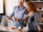 Couple looking at tablet while having breakfast