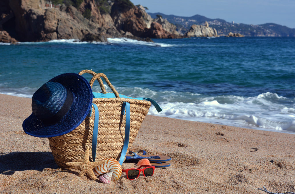 Beach bag with a book and a telephone and sunglasses