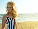 Portrait of chic blond woman in striped dress standing at the seaside and looking aside with provocative green eyes. Femme fatale. Hair care concept. Copy-space. Backlight. Outdoor shot