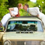 Newlyweds dressed in Ukrainian ethnic clothes kiss over an old c