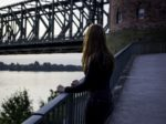 Junge Frau an einer Brcke ber den Rhein